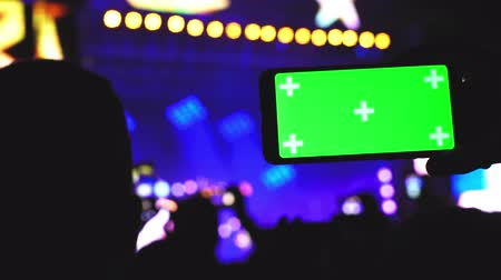 Smartphone green screen chroma key on concert scene party background rave technology concept 4k