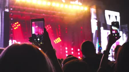 Audience recording video of band on mobile phone in concert