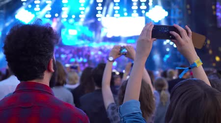 Young couple brunette girl boy casual style taking photos recording video with their smart phones at music concert stage concert beat party rock fest 4k Vídeos