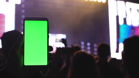 hayranlık : A smartphone with a green screen chromakey on the background of a concert screen and scene light 4k technology