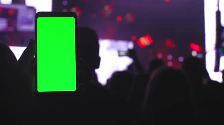 Smartphone with a green screen on the concert background community people using smartphones for video recording at music party festival fest concert 4k technology Vídeos