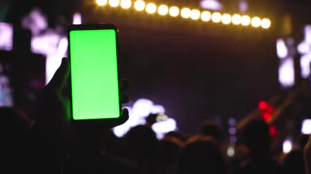 Greenscreen chromakey smartphone on concert, main stage scene highlighted look, hand with smartphone moving across technology party rave background 4k