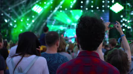 pěvec : Footage of a crowd partying at a rock concert young black-haired man guy with curly hair in a plaid shirt looks, animation motion design friendly shot 4k