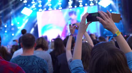 European girl takes a photo video shooting panoramic view look of the concert front of the stage phone technology feelings emotions impressions 4k