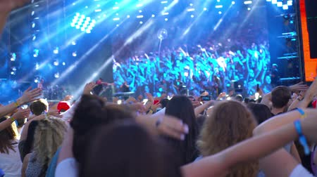 Visitors to the concert shake their hands cheering fans to the music near the stage together night party festival crowd of people silhouettes hands up confetti stroboscope 4k Vídeos