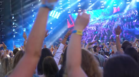 Large crowd of people stage concert synchronously waving their hands to the sound of music open air watching concert or sport event 4k