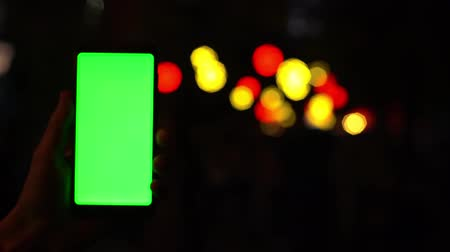 Smartphone with chromakey Green Screen on a background of bokeh blurred street lamps 4k Vídeos