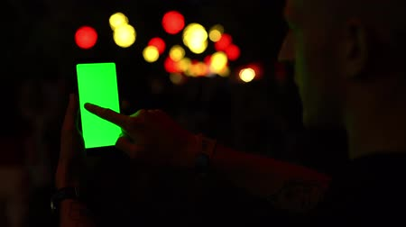 Man using Smartphone with Green Screen chromakey, background of blurred lights bokeh a crowd of people 4k
