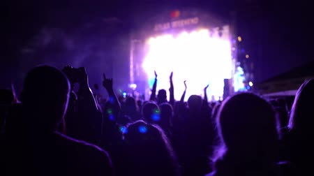 Crowd under the stage portrait, scene highlights flashes bokeh reflections stroboscope, shot of some cheering fans at a rock concert against a background of dynamic lights lanterns 4k