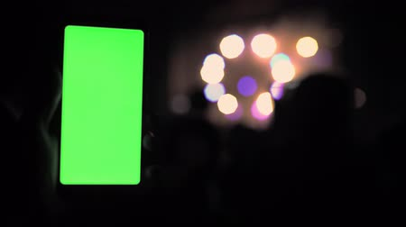 Smartphone chromakey screen tracking technology with a green screen on a background of concert lighting party rave background 4k
