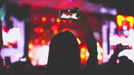 Many young people filming concert on smartphones. Addiction to gadgets, youth problem. Music performance spectators lighting with phones in darkness, relaxing atmosphere. Teenager fans listening music