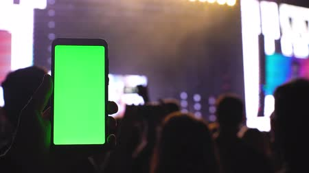 A smartphone with a green screen chromakey on the background of a concert screen and scene light 4k technology