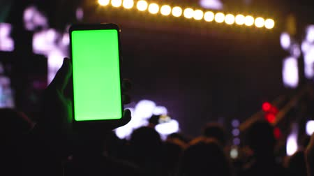 concert crowd : Greenscreen chromakey smartphone on concert, main stage scene highlighted look, hand with smartphone moving across technology party rave background 4k