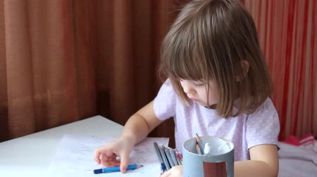Little girl with an intelligent look draws scrawl Dostupné videozáznamy