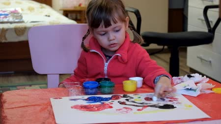 Little girl paints with finger paints