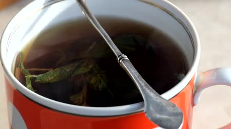 Steam steam curls over a cup of hot tea with mint leaves
