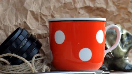 Steam rises over a cup of hot tea. Vintage red cup in white polka dots, twine, old lens from camera