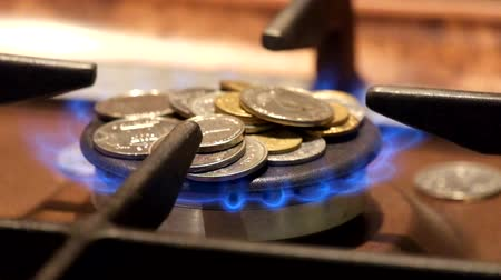 Coins are on a burning gas burner. Not enough money to pay for gas