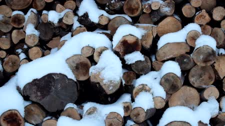 It is snowing, slowly covering the logs with a white cold blanket