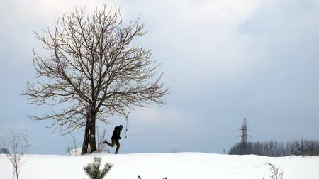 Man runs across a snow-covered field past a lonely tree in slow motion Стоковые видеозаписи