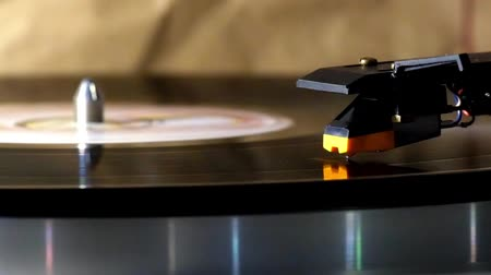 Head-shell cartridge is on a rotating vinyl record. Spinning vinyl record on the stereo turntable