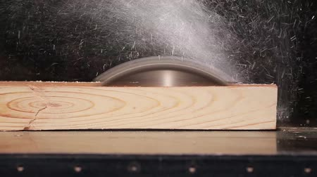 wood : Circular saw cutting wooden plank on a black background Stock Footage