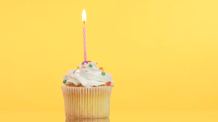 queque : tasty birthday cupcake with one candle, on yellow background