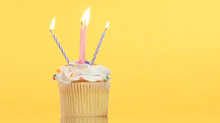 gourmet : tasty birthday cupcake with four candle, on yellow background