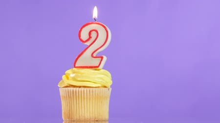 queque : Birthday cupcake with candle number two, on purple background Vídeos