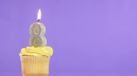queque : Birthday cupcake with candle number eight, on purple background