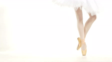 bale : Young ballerina dancing, closeup on legs and shoes, standing in pointe position Stok Video