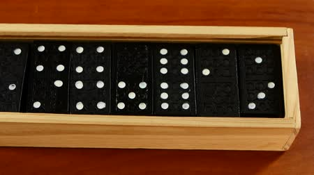 trumna : Box with domino game is opened light box, isolated on wooden surface