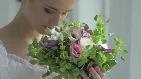 brown dress : Beautifaul blonde girl in vintage white dress with charming bouquet of flowers, smelling, watching at the camera, slow motion