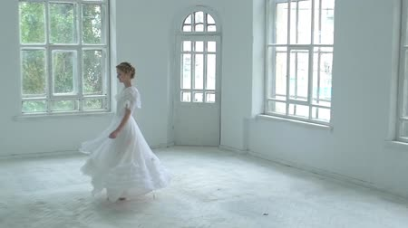 cüppe : Beautiful young girl in white dress whirling in the middle of the room and smiling, slow motion Stok Video