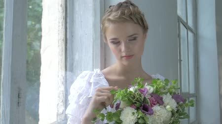 луг : Beautiful young, blonde girl in vintage white dress with bouquet of flowers in her hands sitting on windowsill and watching , touching flowers, smiling, slow motion