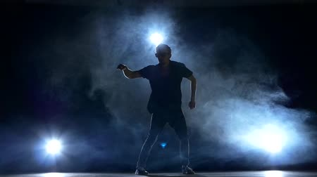 moderní : One hip hop acrobatic break-dancer stylish man in modern sunglasses continue dancing, smoke, silhouette, slow motion