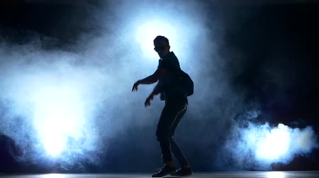 breakdancing : Young hiphop, b-boy dancer starts making a movements, smoke, silhouette, slow motion