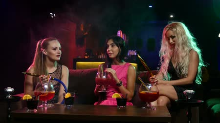 lounge : Group of young and sexy woman smoking hookah in the lounge caffee.  talk to each other Stock Footage