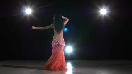 hint : Beautiful, young, attractive and sexy belly dancer perfoming exotic dance in pink dress, on black, back light, slow motion