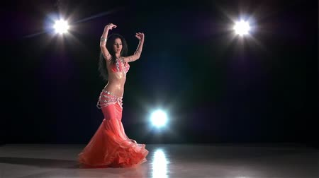 árabe : Belly dance of beautiful, young girl in pink dress, on black background, back light, slow motion Vídeos