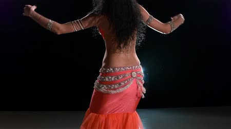 танцоры : Slim torso of a beautiful, young female belly dancer on a black background, back light, slow motion
