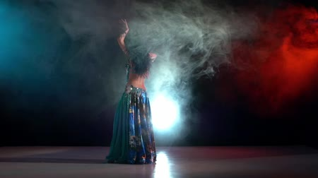 árabe : Talanted belly dance movements of young, great and attractive girl, starting, slow motion, in smoke, black background, blue, red, blue