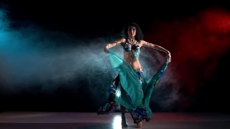 árabe : Exotic, sensetive, belly dance movements of young, great and attractive girl in exotic dress, slow motion, in smoke, black background, blue, red, blue