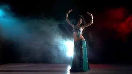 tancerka : Exotic, sensetive, belly dance movements of young, great and attractive girl in exotic dress, slow motion, continue, in smoke, black background, blue, red, blue Wideo