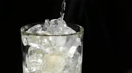 wódka : A cube of ice falling into a glass of water, beautiful splashes on black background. close up. slow motion Wideo
