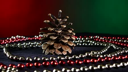 kutluyor : Christmas tree pine cone toy for Christmas tree for decoration Christmas or New Year and red and white beads, rotation, on red and green background Stok Video