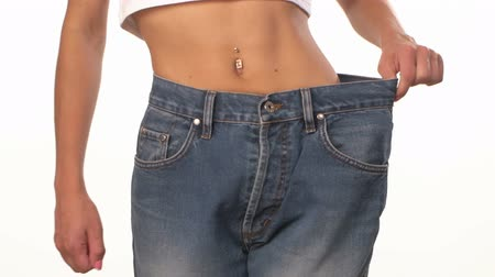 потеря : Slim girl in big jeans, showing her lose weight and spinning, on white background, close up
