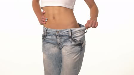 fogyás : Slim girl in big jeans, showing her lose weight and spinning, on white background