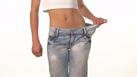 kaybediyor : Sporty girl in big jeans, showing her lose weight and spinning, on white background