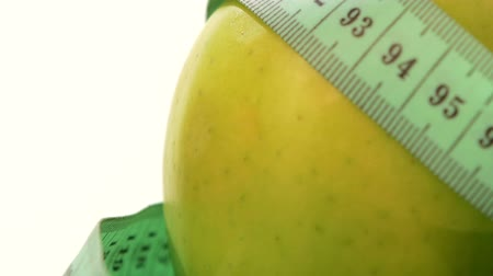 fogyás : Green, juicy and fresh apple with measuring tape on white background, rotation, close up
